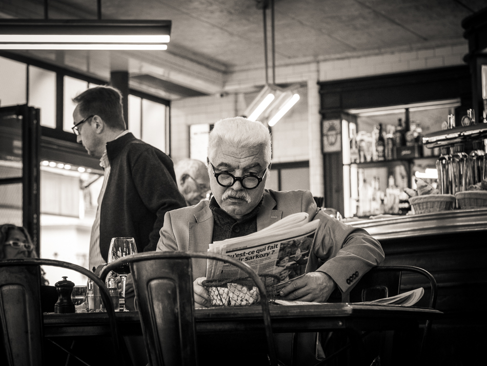 Black and white photograph of a Parisian man reading newspaper in a bistro